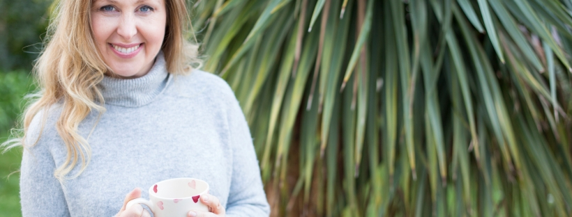 Profile photo of Lorraine Pannetier outside by palm tree holding a cup of tea and wearing a grey jumper and smiling at the camera.