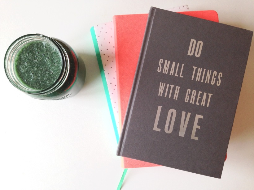 Green smoothie and pile of coloured notebooks. The top book has 'Do small things with great love' on the front.