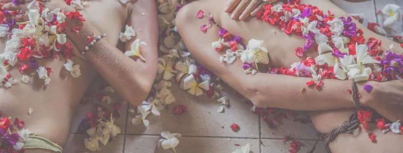 Two women laying on the floor covered in flower petals