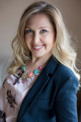 Lorraine Pannetier profile picture. Navy jacket, pink shirt and colourful necklace.